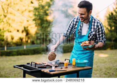 Handsome Young Man Preparing Barbecue For Friends