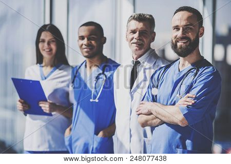Team Of Professional Doctors With Medical Devices In Uniform Standing In Hospital. Nurse And Doctor