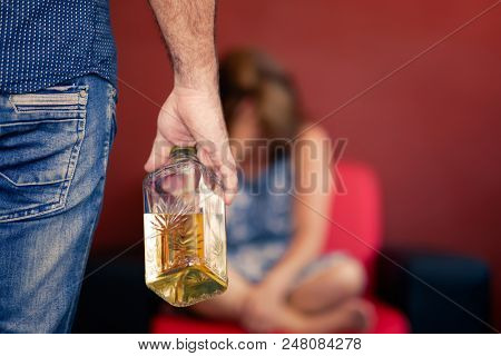 Drunk man holding a bottle of liquor with a sad and worried out of focus wife on the background