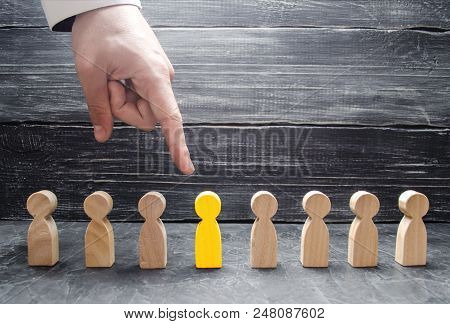 A Businessman's Hand Points To A Wooden Human Figure. The Concept Of The Search For Workers, Managem