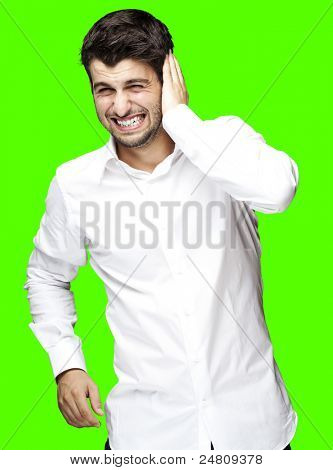 portrait of young man covering his ear against a removable chroma key background