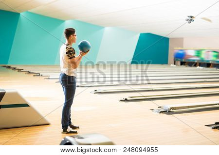 Full Length Side View Of Confident Teen Boy Practicing Bowling In Club