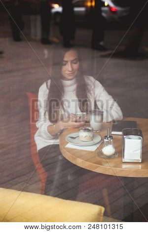 Charming Woman Looks On The Phone In Cafe. Tasty Chocolate Cake And Coffee On The Table. Bright Sunn