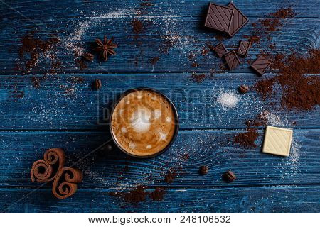 Cup Of Cappuccino Like Part Of Macrocosm, Top View On The Blue Table