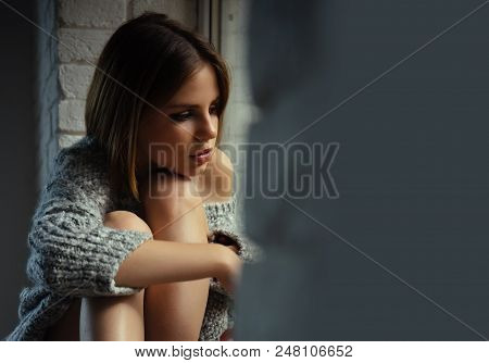 Woman With Makeup On Pretty Face Look Throught Window. Woman Sit With Legs On Window Sill. Pretty Wo