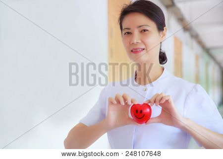 Smiling Red Heart Held By Smiling Female Nurse's Hand In Health Care Hospital Or Clinic. Professiona