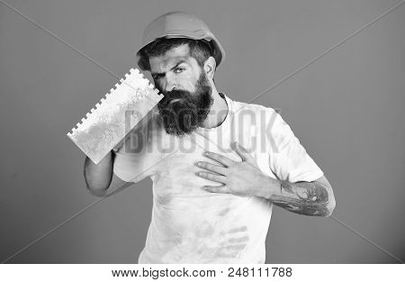 Modern repairman concept. Painter, plasterer, repairman, foreman in helmet or hard hat holds putty knife or plastering tool. Bearded repairman with serious face and dirty shirt on red background. poster