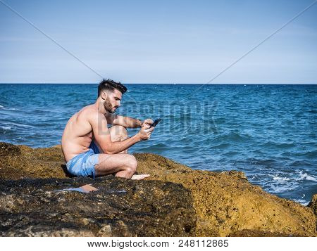 Shirtless Young Man Drying Off In Hot Sun Reading Using An Ebook Reader To Read, Muscular Man Wearin