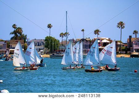 July 2, 2018 In Newport Beach, Ca:  People Sailing In Small Sail Boats Called A Dinghy Boat Taken In