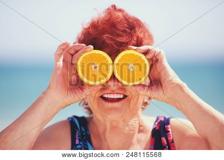 Funny Portrait Of Happy Mature Woman, Grandma Having Fun With Orange Eyes On Summer Vacation. Active