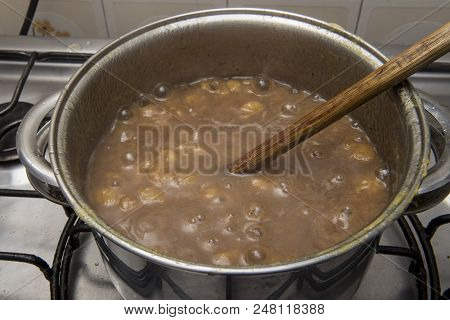 Sweet Banana Being Cooked In A Stainless Steel Pan In A Sugar Syrup