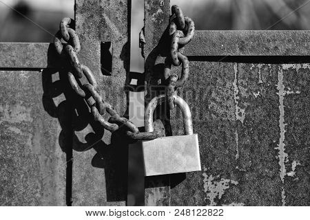 old lock. Padlock with shackle and locking mechanism closeup one portable lock on chain on unpainted rusty metal gate doors outdoor on blurred background poster