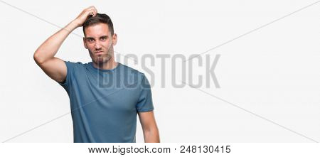 Handsome young casual man confuse and wonder about question. Uncertain with doubt, thinking with hand on head. Pensive concept.