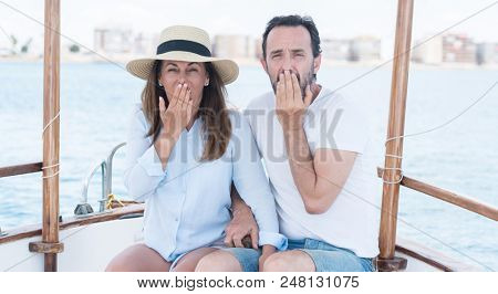 Middle age couple traveling on sailboat cover mouth with hand shocked with shame for mistake, expression of fear, scared in silence, secret concept