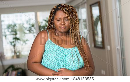 African american woman at home with hand on stomach because indigestion, painful illness feeling unwell. Ache concept.
