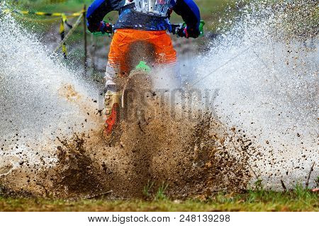 Enduro Rides Through The Mud With Big Splash,driver Splashing Mud On Wet And Muddy Terrain,motocross