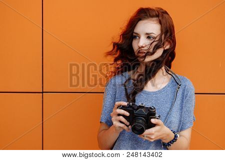 Beautiful Girl With Windy Hair Using A Vintage Film 35mm Camera In Front Of Orange Wall With Copyspa