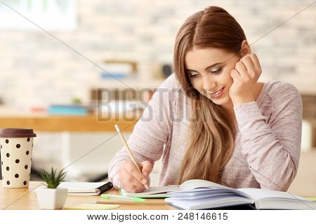 Teenage girl with stuff for studying at table indoors