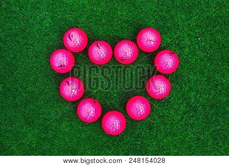 Golf Pink Balls On Green Grass Course In A Shape Of Heart. Loving Golf Concept.