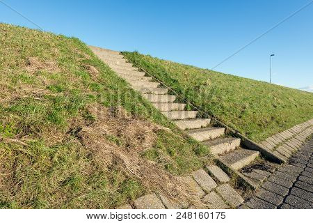 Concrete Staircase On A Dutch Dike Covered With Grass. It Is A Sunny Day And Some Grass Is Dry And Y