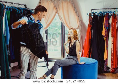 Young Attractive Woman Choosing A New Stylish Dress For Herself, Male Couturier Helps Her To Make A
