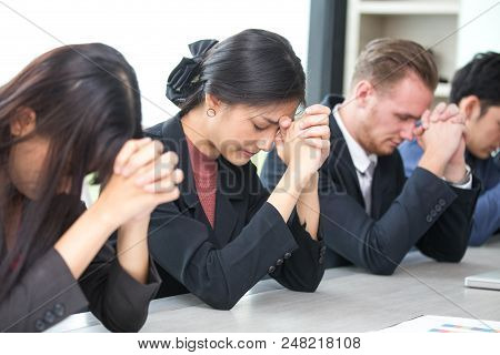 Business People Pray Together At Meeting Room. People In Situation Concept.