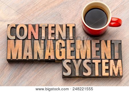 content management system - word abstract in vintage letterpress wood type blocks with a cup of coffee