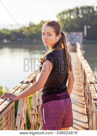 Sport And Fitness. Young Woman Training Outdoor At Sunrise With Urban Background.