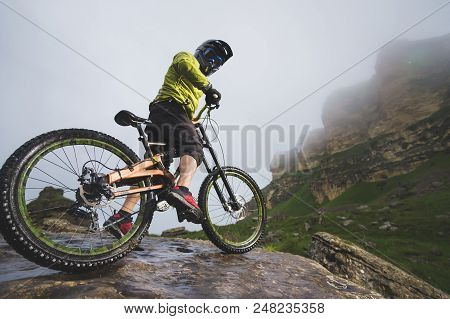 Portrait Of A Man Aged On A Mountain Bike In The Mountains In Cloudy Weather. Mountain Bike Concept.