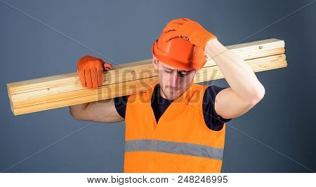 Safety And Protection Concept. Man In Helmet, Hard Hat And Protective Gloves Holds Wooden Beam, Grey