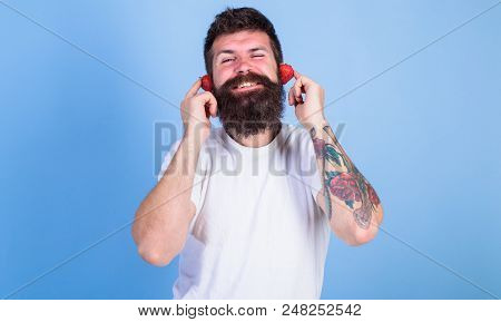 Man Bearded Hipster Red Ripe Strawberry Ears As Headphones. Summer Top Radio Chart. Guy Enjoy Juicy