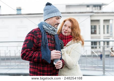 Embarrassed Guy With Coffee Cup In Hand. Sweet Aged Couple Meet On Street. Woman Pleased Guy About C