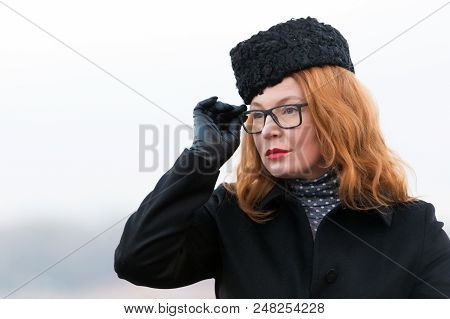 Portrait Of Woman In Glasses And Black Coat. Concentrated Rad Hair Woman In Hat. Portrait Of Busines
