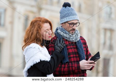 Couple Reads Message In Smart-phone. Woman Embraces Man With Cellular. Guy In Hat And Glasses Receiv