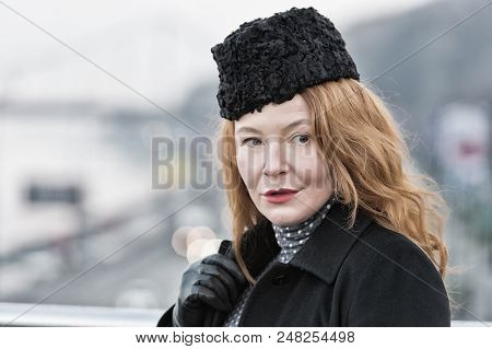 Close-up Of Women In Black Coat And Black Hat On Street. Close-up Of Rude Women With Piercing Glance