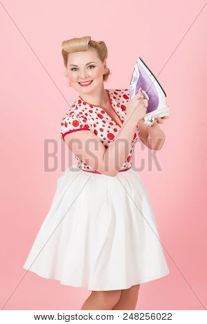 Young Pin-up Styled Girl Holds Iron On Pink Background. Beautiful Pin-up Blonde Woman With Curls Pre