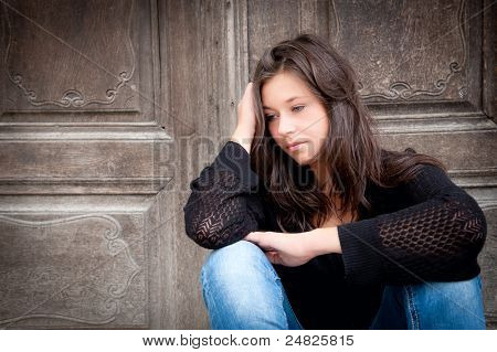 Outdoor portrait of a sad teenage girl looking thoughtful about troubles poster