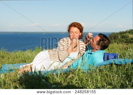 Attractive Couple Have A Rest In The Grass Near Of Big Lake. Loving Couple In Summer Day. Happy Lyin