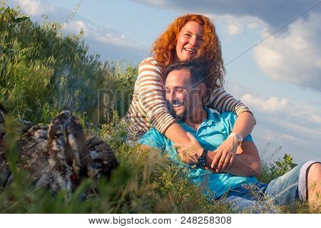 Happy Loving Smile Attractive Couple Laying By Bonfire Hugging In Grass And Clouds. Couple Loves Cas