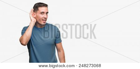 Handsome young casual man smiling with hand over ear listening an hearing to rumor or gossip. Deafness concept.