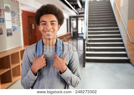 Portrait Of Male High School Student Standing By Stairs In College Building