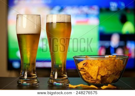 beer glasses and chips in front of tv - watching football at home - soccer supporters