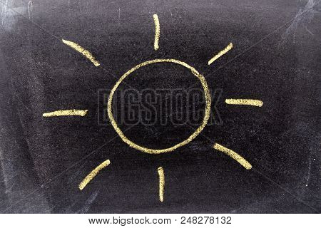 Yellow Color Chak Hand Drawing In Sun With Ray Shape On Blackboard Background