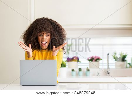 African american woman using computer laptop at kitchen very happy and excited, winner expression celebrating victory screaming with big smile and raised hands