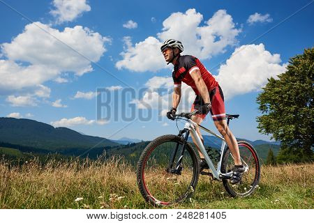 Athletic Sportsman Cyclist In Sportswear And Helmet Riding A Bicycle In High Grass. Active Male Bike