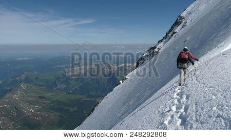 Mountain Guide And Client On A Steep North Face Slope Heading Towards The Summit With A Great View O