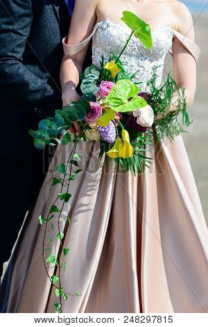 Unidentified Young Wedding Couple. Stylish Bride And Groom Standing With Brides Bouquet Outside On S