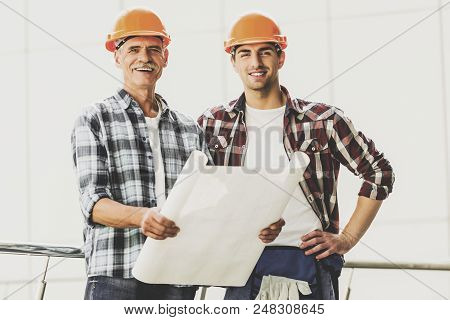 Two Industrial Engineers In Shirts And Helmets Works With Blueprint In Office. Modern Construction A