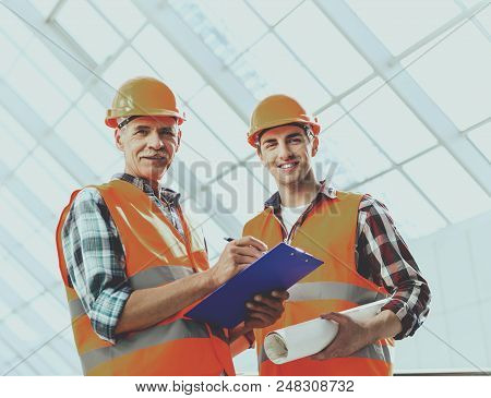 Industrial Engineers Makes Notes And Works With Blueprint In Office. Modern Construction And Enginee