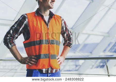Close Up. Industrial Engineer In Yellow Vest And Shirt Stands In Office. Modern Construction And Eng